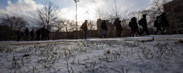 Close up photo showing blades of grass sticking up through snow with silhouettes of students walking in the background